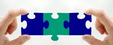 Photo of person holding three interlocking puzzle pieces